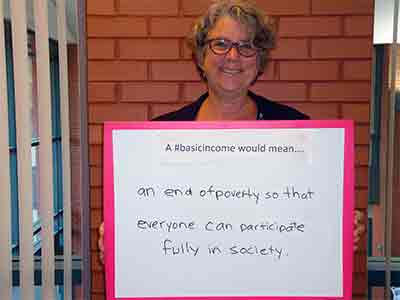 Woman holds up sign with text: A #basicincome would mean....an end of poverty so that everyone can participate fully in society.