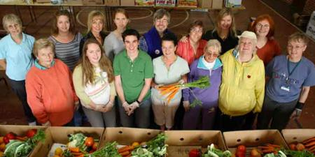 JustFood volunteers and staff posing for a picture in front of packed produce boxes