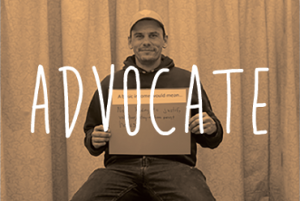 Image of man holding sign with orange overlay. Text reads: ADVOCATE
