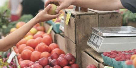 Photo of a farmers market vendor handing an apple to a customer